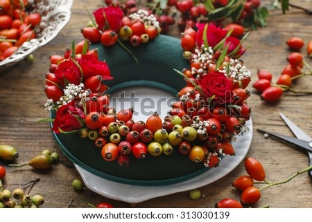 Florist at work: steps of making door wreath with rose hip, hawthorn and rowan berry - stock photo