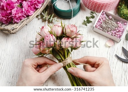 Florist at work: woman making bouquet of pink roses. - stock photo