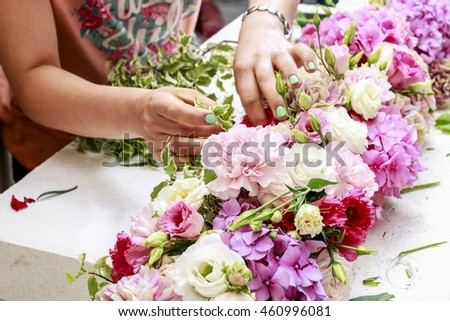 Florist at work: woman making floral arrangement with carnation, eustoma and hortensia flowers.