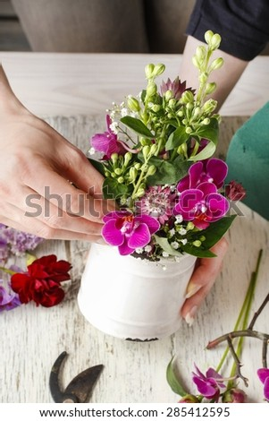 Florist at work. Woman making floral arrangement with orchid flowers and gypsophila paniculata, copy space