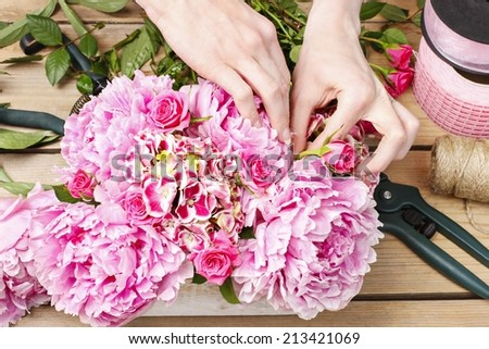 Florist at work: woman making floral decoration of pink peonies - stock photo