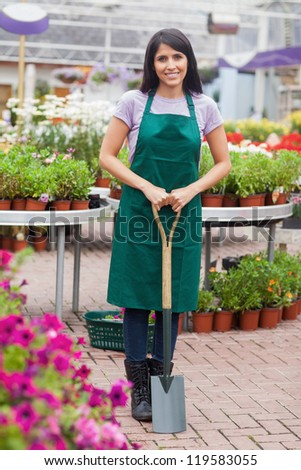 Florist holding a spade while smiling - stock photo