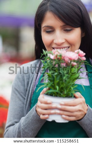 Florist holding flower while smelling it in garden centre - stock photo
