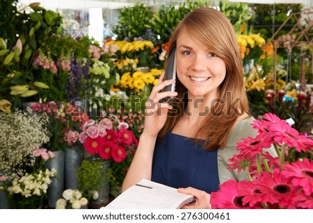 Florist In Shop Taking Order Over The Phone In Shop - stock photo