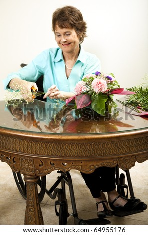 Florist in wheelchair trimming baby's breath with a pair of shears. - stock photo