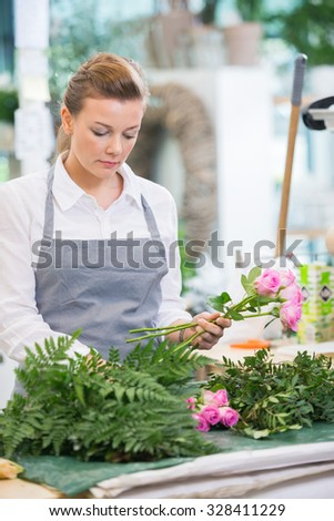 Florist making bouquet of fresh roses at counter in flower shop - stock photo