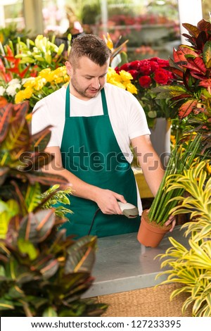 Florist man reading barcode potted plant shop market flower - stock photo