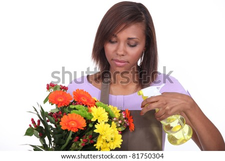 Florist spraying a bunch of flowers with water - stock photo