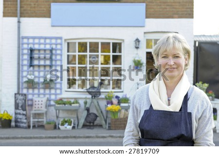 Florist standing outside her shop smiling at camera
