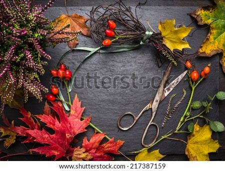 Florist table for Making autumn decorations with leafs,shears and ribbon, fall background with copy space - stock photo