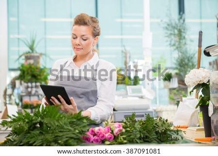 Florist Using Digital Tablet In Flower Shop - stock photo