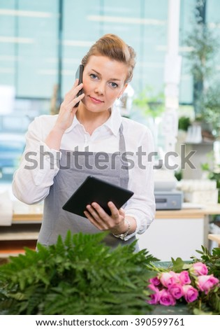 Florist Using Mobile Phone And Digital Tablet In Flower Shop - stock photo