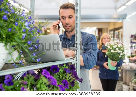 Florist Using Mobile Phone And Laptop In Shop - stock photo