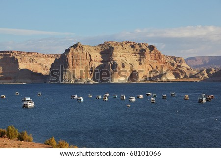 Flotilla of elegant white yachts on Lake Powell. Small waves on the lake from the evening breeze - stock photo