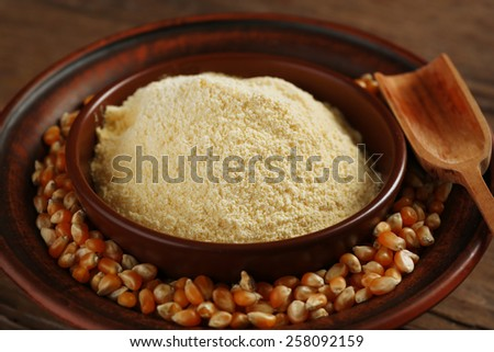 Flour and corn grains in bowls with spoon on wooden background - stock photo