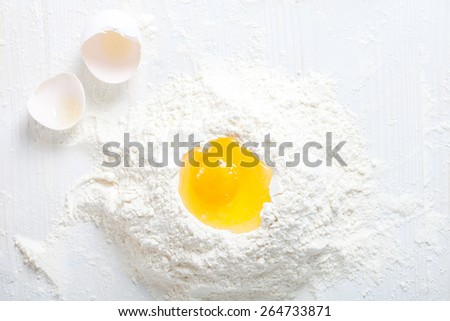 Flour and eggs. Hands kneading dough on board - stock photo