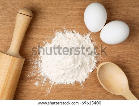 Flour and eggs on a wooden board - stock photo