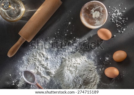 flour and ingredients on black table. Top view - stock photo