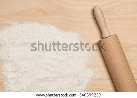 flour and rolling pin on wooden background