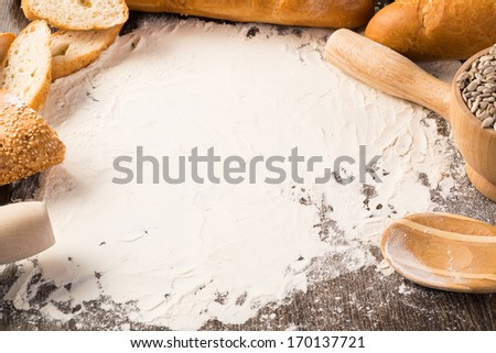 flour and various white bread on a wooden surface - stock photo