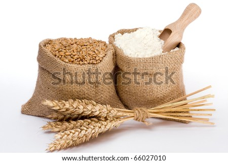 Flour and wheat grain in small burlap sacks - stock photo