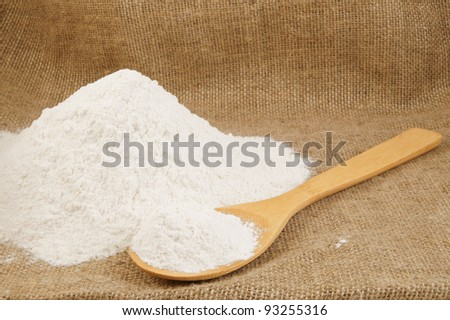 Flour and wooden spoon on jute hessian background - stock photo