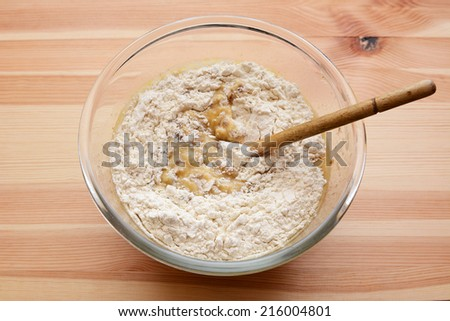 Flour being stirred into wet batter for banana loaf, in a glass bowl on a wooden table - stock photo