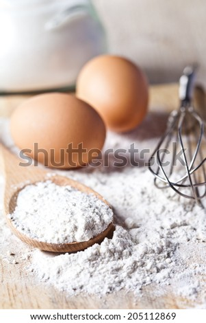 flour, eggs and kitchen utensil on a wooden board  - stock photo