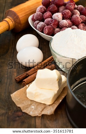 flour, eggs, cherries, butter, cinnamon on a wooden table. A set of products for baking the cake with cherries. View from above.