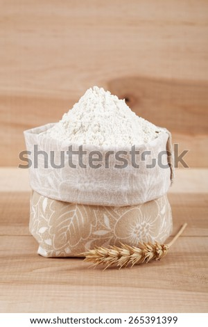 Flour in a canvas bag and ear of wheat on the wooden board. - stock photo