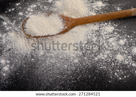 Flour in a old  wooden spoon. Selective focus