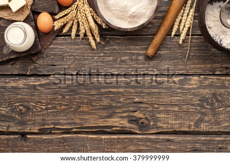 flour in a wooden bowl on dark wooden background with spikelets of wheat, eggs, milk and butter, top view with copy space. ingredients for bakery products - stock photo