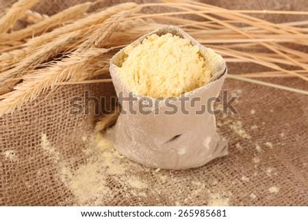 Flour in bag with wheat ears on burlap cloth, closeup - stock photo