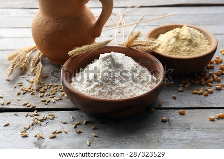 Flour in bowls with grains on wooden background - stock photo
