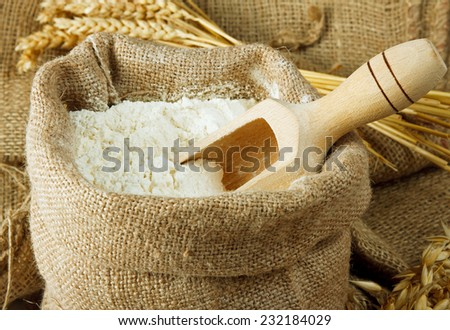 Flour in burlap bag and wooden spoon  - stock photo