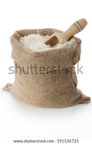 Flour in burlap bag on white background