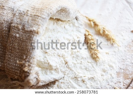 Flour in burlap bag on wooden cutting board background - stock photo
