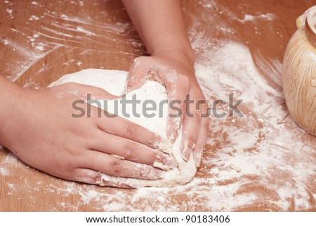 Flour in capacity with dough and rolling pin on the wooden table