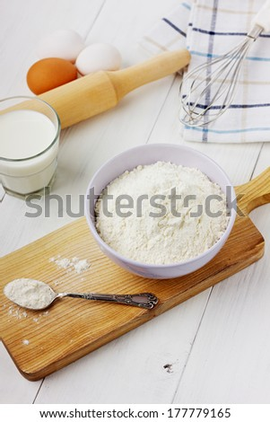Flour in ceramic bowl with eggs and rolling pin on a white background - stock photo