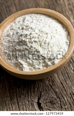 flour in wooden bowl on wooden table