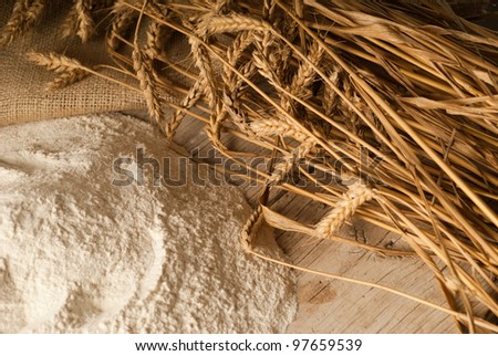 Flour powder on a wooden table garnished with wheat - stock photo