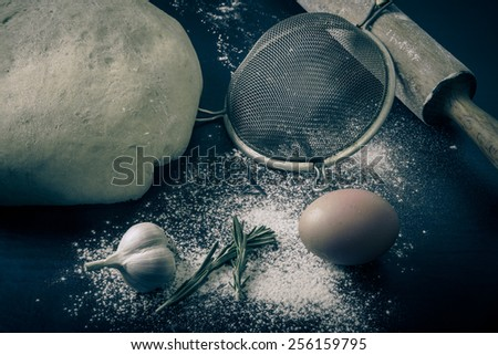 Flour, rolling pin, egg, rosemary, garlic and dough for pie. Toned. - stock photo