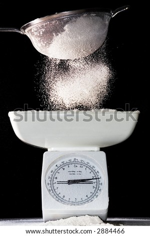 Flour sifted onto scales - stock photo