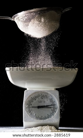 flour sifted onto scales (side lit) - stock photo