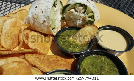 Flour tortilla wrap stuffed with rice and vegetables served with potato chips and salsa - stock photo
