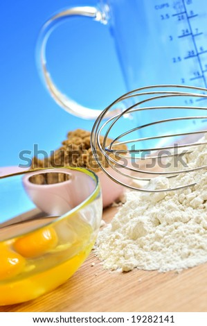 Flour, whisk and eggs in a bowl, baking ingredients - stock photo