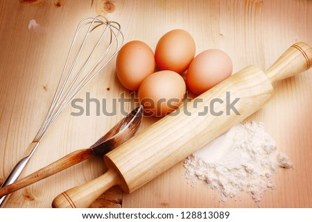 Flour with eggs and rolling pin over white background - stock photo