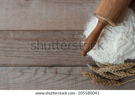 Flour with wheat and rolling pin on old wooden table - stock photo