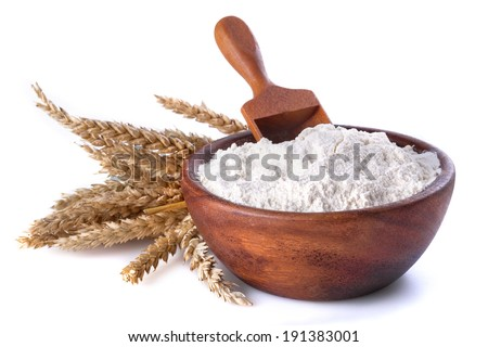 flour with wheat in a wooden bowl and shovel on a white background - stock photo