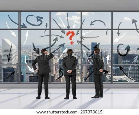 Flow chart of the brainstorming process. Arrow, question mark and three young businessmen in an office space. - stock photo
